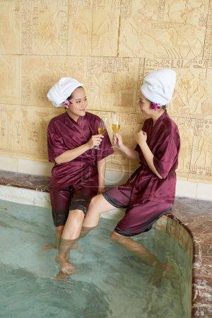 Photo pour Jeunes femmes asiatiques en robes et serviettes sur la tête en buvant du champagne et en se parlant dans la piscine - image libre de droit