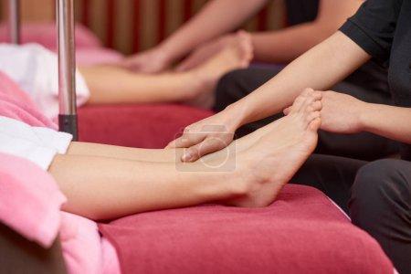 Photo pour Gros plan de jeune femme couchée et la réception décontractée massage pour ses pieds au salon de beauté - image libre de droit