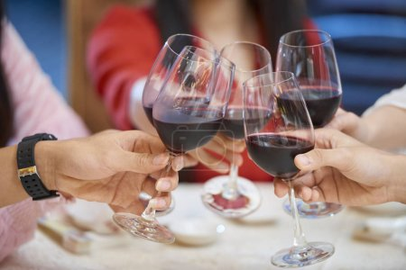 Photo for Close-up image of people clinking with wine glasses over dinner table - Royalty Free Image
