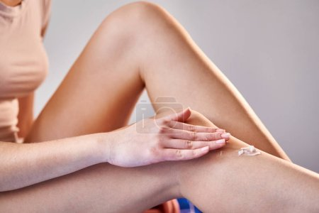 Photo for Close-up of woman sitting and applying lotion on her beautiful legs after bathroom - Royalty Free Image