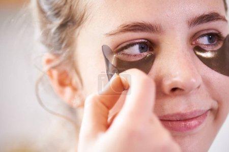 Photo pour Gros plan du visage de femme à l'aide de pansements oculaires pour maintenir la beauté de la peau - image libre de droit