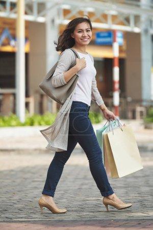 Photo pour Assez heureuse jeune femme avec des sacs en papier-marchant dans la rue après le shopping toute la journée - image libre de droit
