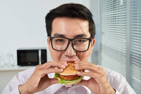 Photo for Young entrepreneur in glasses eating hamburger lunch in office - Royalty Free Image