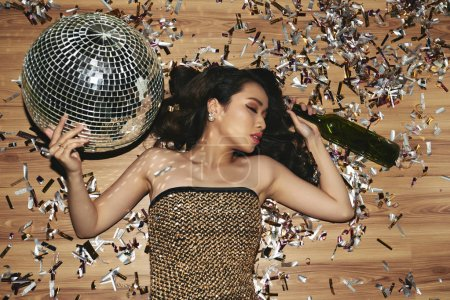 Beautiful young woman fell asleep on the floor with wine bottle and disco ball