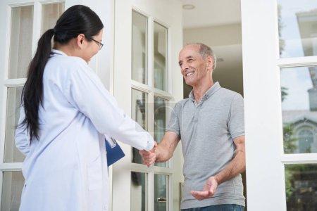Ärztin mit Klemmbrett schüttelt Seniorin beim Hausbesuch beim Betreten des Hauses die Hand
