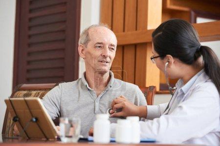 Photo pour Femme professionnelle en robe blanche écoutant le rythme cardiaque d'un patient âgé avec stéthoscope assis à table - image libre de droit