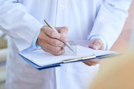 Photo for Close-up of male doctor in lab coat filling in medical form or prescribing a medicine - Royalty Free Image