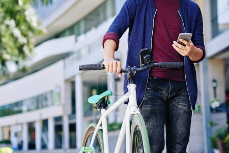 Photo for Cropped image of man with smartphone walking with bicycle in the street - Royalty Free Image
