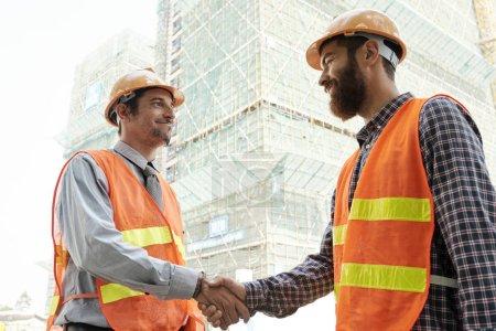 Photo pour Travailleurs de la construction souriants serrant la main pour se saluer avant le jour du jour ouvrable - image libre de droit