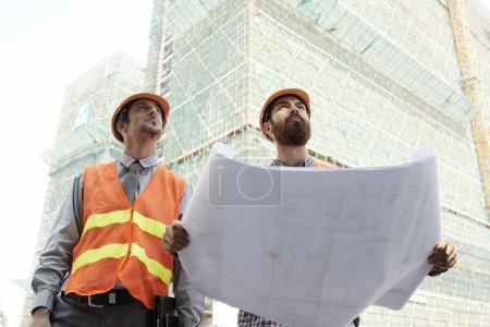 Photo pour Deux ingénieurs professionnels déploient un plan directeur en papier lorsqu'ils regardent un gratte-ciel - image libre de droit