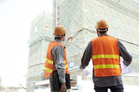 Photo pour Entrepreneur pointant vers le bâtiment pour expliquer quelque chose au travailleur de la construction - image libre de droit