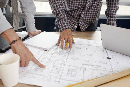 Photo pour Équipe d'ingénieurs en construction discutant du plan directeur en papier sur la table de bureau - image libre de droit