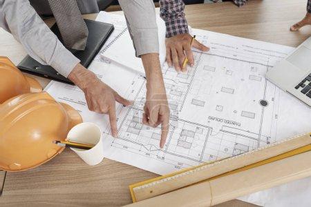 Photo pour Mains d'architectes vérifiant les mesures de chaque mur de la maison sur laquelle ils travaillent - image libre de droit