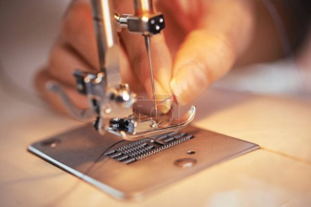 Photo for Closeup shot of hand of anonymous tailor putting thin thread in needle of modern sewing machine in workshop - Royalty Free Image