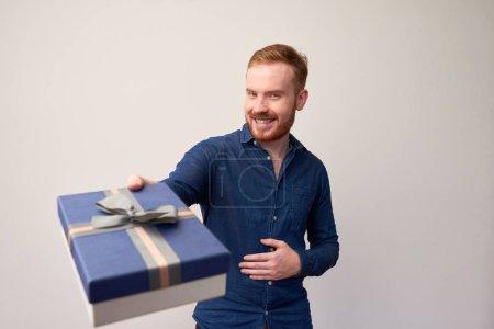 Photo pour Portrait d'un bel homme roux en tenue décontractée donnant une boîte cadeau et souriant à la caméra sur fond blanc - image libre de droit