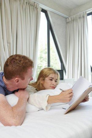 Photo pour Jeune homme regardant sa petite amie écrire des plans et ides dans le journal - image libre de droit