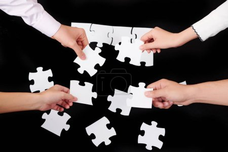 Close-up of people collecting puzzles in team over black background