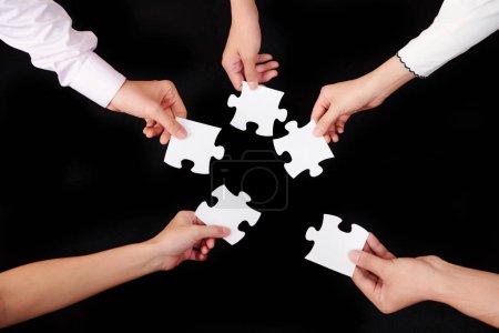 Photo pour Gros plan de gens d'affaires tenant des pièces de puzzles et essayant de les connecter sur fond noir - image libre de droit