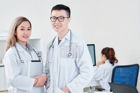 Photo for Portrait of smiling young Vietnamese general practitioners in white labcoats, their colleague working on computer in background - Royalty Free Image