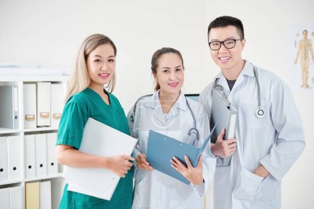 Photo for Team of Vietnamese medical workers in scrubs and labcoats posing with document folders - Royalty Free Image