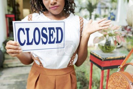 Photo for Portrait of young owner standing and holding Closed sign she closing the store - Royalty Free Image