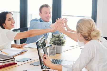 Foto de Grupo de empresarios sentados a la mesa juntos y dando un máximo de cinco entre sí durante la exitosa reunión de negocios - Imagen libre de derechos