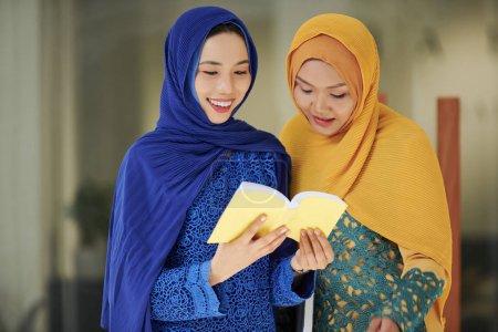 Photo pour Souriant jolies jeunes femmes musulmanes vietnamiennes lisant ensemble le livre sacré - image libre de droit