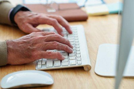 Photo pour Mains de l'homme d'affaires principal ou ingénieur logiciel tapant sur le clavier lorsque vous travaillez sur l'ordinateur à sa table de bureau - image libre de droit