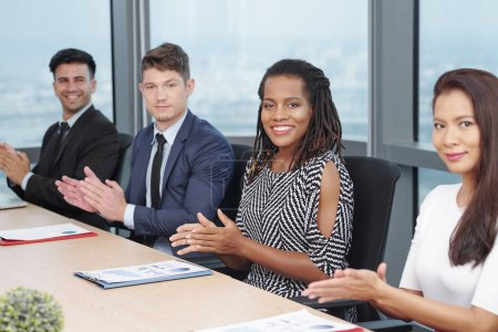 Photo for Cheerful multi-ethnic business people sitting at meeting table and applauding - Royalty Free Image