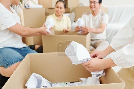 Photo pour Emballage familial de vaisselle fragile dans du papier lors de l'emballage des choses dans des boîtes en carton - image libre de droit