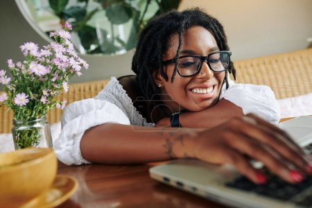 Photo for African happy woman in eyeglasses sitting at the table and typing on laptop during her leisure time at home - Royalty Free Image