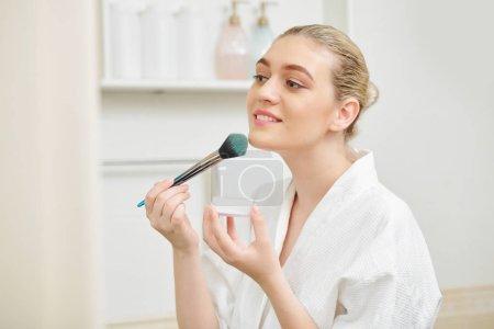Photo pour Jolie jeune femme positive appliquant de la poudre minérale visage avec des professions pinceau - image libre de droit