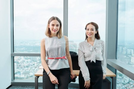 Photo for Beautiful smiling elegant businesswomen leaning on table in modern office and looking at camera - Royalty Free Image