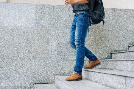 Photo pour Image recadrée de l'homme en jeans avec un gros sac à dos descendant les escaliers et tenant une tasse de café à emporter - image libre de droit