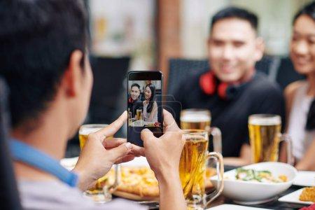 Photo pour Vue arrière d'un jeune homme photographiant ses amis sur son téléphone portable alors qu'ils dînent au restaurant - image libre de droit