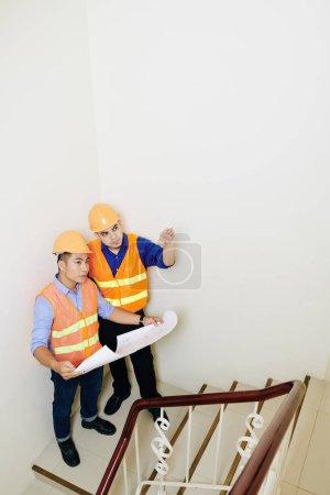 Photo pour Équipe d'entrepreneurs avec un plan directeur discutant vol des escaliers dans le nouveau bâtiment - image libre de droit