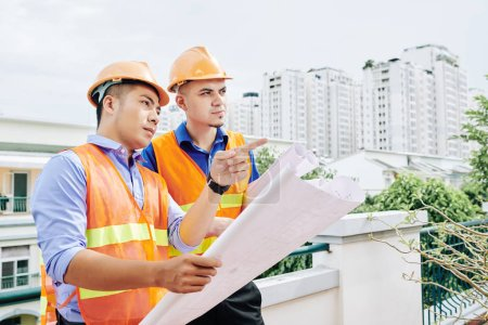 Photo pour Travailleurs de la construction sérieux debout à l'extérieur avec le plan de construction et discuter de la séquence des travaux qui doit être fait aujourd'hui - image libre de droit