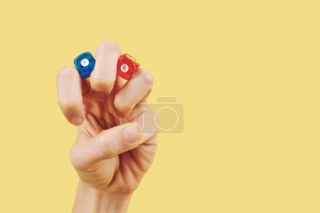 Photo for Hand of person with red and blue dice between fingers on yellow background - Royalty Free Image