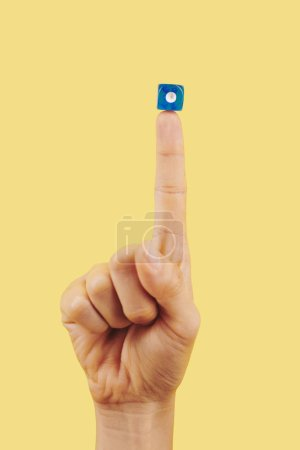 Photo for Blue dice with one dot on index finger of person, gambling and good luck concept - Royalty Free Image