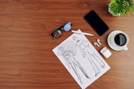 Photo for Fashion drawings on table of designer with cup of coffee, smartphone and glasses - Royalty Free Image