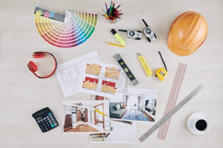 Photo for Table of professional architect with photos of interior visualization, house blueprint, hardhat and color palette - Royalty Free Image