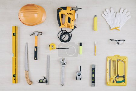 Photo for Set of construction tools on wooden table including spirit level, hammer, electric jigsaw and spanner wrench - Royalty Free Image