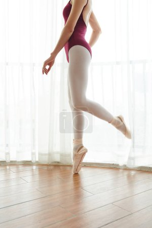 Photo for Cropped image of ballet dancer training in leotard ballet slippers in studio - Royalty Free Image
