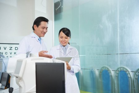 Photo for Smiling assistant showing medical history of patient to ophthalmologist - Royalty Free Image