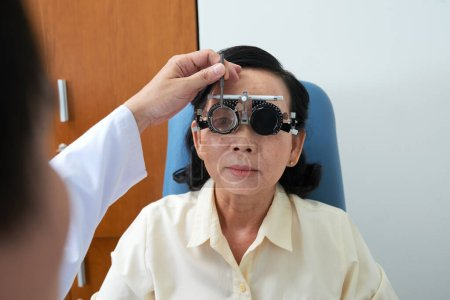 Photo for Doctor using adjustable optical trial lens frame when checking eyesight of senior woman - Royalty Free Image