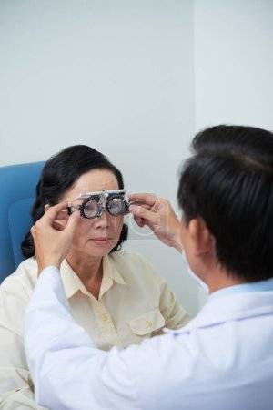 Photo for Ophthalmologist helping senior patient to wear adjustable optical trial lens frame when checking her eyesight - Royalty Free Image