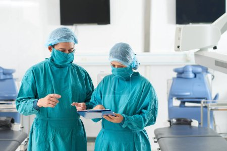 Photo pour Chirurgien asiatique et son assistant en uniforme discutant des détails de la chirurgie à venir ou des antécédents médicaux - image libre de droit