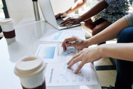 Photo pour Image rapprochée de gestionnaires financiers discutant de tableaux et de rapports lors d'une réunion au bureau - image libre de droit