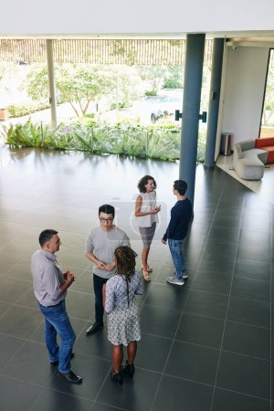 Photo for Business people standing in office hall and discussing work moments and ideas - Royalty Free Image