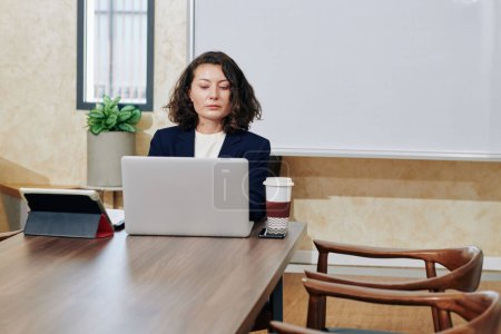 Photo for Serious confident serious female entrepreneur working on laptop at her office and checking e-mails from partners - Royalty Free Image